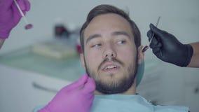 Retrato do close-up do homem assustado novo na boca da coberta do escritório do dentista com mãos Mãos do doutor e da enfermeira vídeos de arquivo