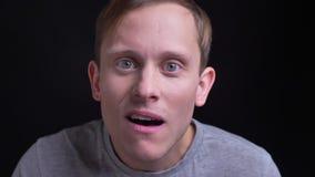 Retrato do close up do homem caucasiano atrativo novo que está sendo surpreendido e excitado olhando a câmera com fundo video estoque