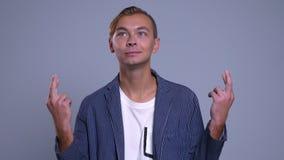 Retrato do close up do homem caucasiano novo esperançoso que é nervoso e que tem seus dedos cruzados vídeos de arquivo
