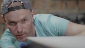 Retrato do close-up do homem concentrado no tampão, envolvido em seu trabalho O trabalhador gloved que verifica e que mede seu vídeos de arquivo