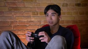 Retrato do close up do homem coreano novo que joga os cames video usando o console que senta-se no saco de feijão dentro video estoque