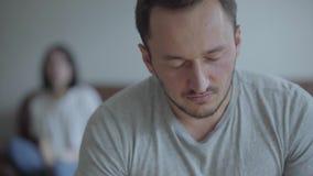 Retrato do close-up do homem de grito no primeiro plano e de sua esposa irritada da gritaria que senta-se no sofá no fundo video estoque