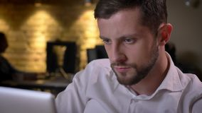 Retrato do close up do homem de negócios caucasiano adulto focalizado que trabalha no portátil no escritório no local de trabalho video estoque