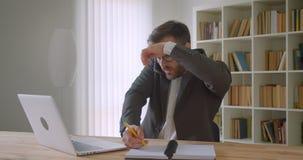 Retrato do close up do homem de negócios caucasiano considerável adulto nos vidros usando o portátil e tendo uma tomada do telefo video estoque