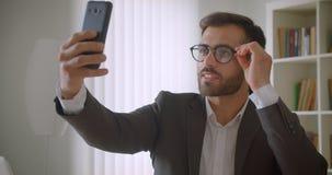 Retrato do close up do homem de negócios caucasiano farpado considerável adulto nos vidros que mandam um vídeo chamar o telefone  vídeos de arquivo