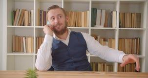 Retrato do close up do homem de negócios caucasiano novo que tem um telefonema no escritório dentro com as estantes no filme