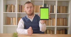 Retrato do close up do homem de negócios caucasiano novo que usa a tabuleta e mostrando a tela verde do croma à câmera no escritó filme