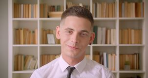 Retrato do close up do homem de negócios seguro novo que olha a câmera que sorri felizmente na biblioteca dentro com estantes sob video estoque