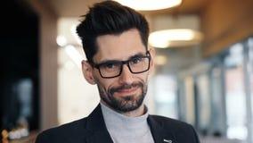 Retrato do close-up do homem de negócios triguenho farpado atrativo que sorri no café vídeos de arquivo