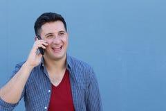 Retrato do close up, homem ectático feliz novo com a boca largamente aberta que fala no telefone celular, isolado no fundo azul foto de stock royalty free