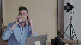 Retrato do close up Homem sociável criativo considerável que fala no telefone com muitas emoções positivas Ele que bebe filme