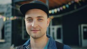 Retrato do close-up do indivíduo novo de sorriso que veste o tampão na moda que está fora filme