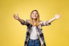 Retrato do close up, jovem mulher que faz sinal com braços para vir dar-lhe um abraço de urso, isolado no fundo amarelo fotos de stock