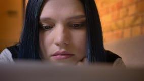 Retrato do close up do moderno caucasiano bonito novo fêmea com o cabelo tingido que surfa a Web no portátil ao encontrar-se sobr vídeos de arquivo