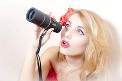 Retrato do close up na vista espreitando da mulher loura nova bonita do pinup do encanto do telescópio do telescópio pequeno na m Imagem de Stock Royalty Free