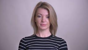Retrato do close up do provérbio de inclinação fêmea caucasiano louro atrativo adulto que olha sim a câmera com fundo video estoque