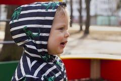 Retrato do close-up do rapaz pequeno de sorriso que joga fora no campo de jogos, criança bonito em uma capa que joga fora cópia Fotos de Stock Royalty Free