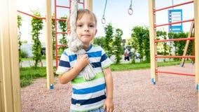 Retrato do close up do rapaz pequeno feliz de sorriso adorável no campo de jogos das crianças no parque foto de stock royalty free