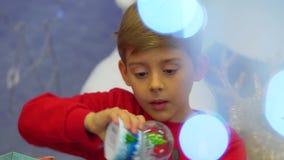 Retrato do close-up do rapaz pequeno que abre o presente de Natal, recebendo o globo da neve e jogando felizmente com ele filme