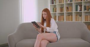 Retrato do close up do ruivo bonito novo fêmea usando a tabuleta que senta-se no sofá em um apartamento acolhedor filme