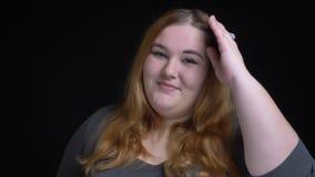 Retrato do close up do sorriso flertando fêmea caucasiano excesso de peso novo seductively e de morder seu bordo ao olhar video estoque