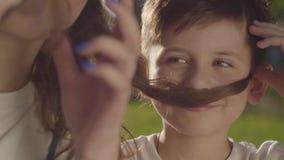 Retrato do close-up do tempo mais velho da despesa da irmã com irmão mais novo fora O menino e a menina que fazem os bigodes fals filme