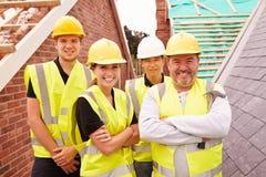 Retrato do construtor On Building Site com aprendizes fotografia de stock