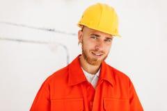 Retrato do construtor de sorriso novo na roupa de trabalho e no yel alaranjados foto de stock royalty free