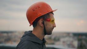 Retrato do construtor feliz e seguro do arquiteto com o capacete de segurança no canteiro de obras, caminhada no telhado filme