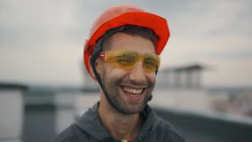 Retrato do construtor feliz e seguro do arquiteto com o capacete de segurança no canteiro de obras, sorrindo na câmera filme