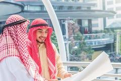 Retrato do coordenador árabe que fala sobre o trabalho da construção e para verificar o modelo com compromisso ao sucesso na baix foto de stock