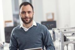 Retrato do coordenador alegre considerável que levanta em seu escritório imagem de stock royalty free