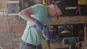 Retrato do coordenador do artesão centrado sobre o furo de um furo com a ferramenta no fundo de uma oficina pequena Conceito de video estoque