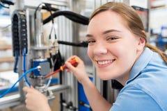 Retrato do coordenador fêmea Working On Machine do aprendiz em Fac imagens de stock