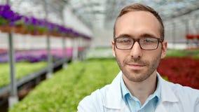 Retrato do coordenador positivo da agricultura do homem nos vidros e no uniforme que levantam na estufa filme
