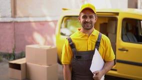 Retrato do correio de sorriso com posição da prancheta perto da camionete amarela filme