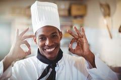 Retrato do cozinheiro chefe feliz que faz o sinal aprovado Fotografia de Stock