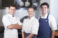Retrato do cozinheiro chefe And Staff Standing pelo fogão na cozinha imagem de stock