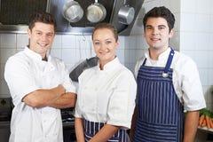 Retrato do cozinheiro chefe And Staff Standing pelo fogão na cozinha foto de stock royalty free
