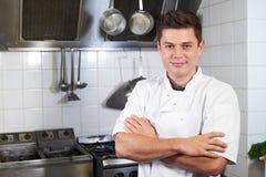 Retrato do cozinheiro chefe Wearing Whites Standing pelo fogão na cozinha fotos de stock
