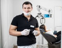 Retrato do dentista masculino considerável que guarda ferramentas dentais - sonde e espelhe no escritório dental dentistry imagem de stock royalty free