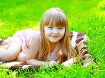 Retrato do descanso de encontro de sorriso bonito da criança na grama Imagens de Stock Royalty Free