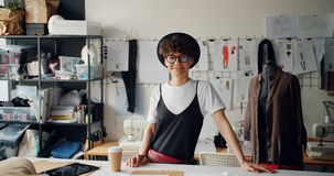 Retrato do desenhador de moda bonito da mulher que sorri no estúdio que olha a câmera vídeos de arquivo