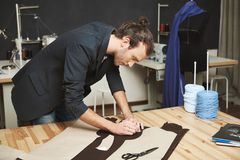 Retrato do desenhista de roupa bonito viril do homem adulto com penteado à moda no terno preto que corta partes de foto de stock royalty free