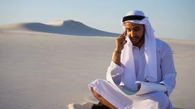 Retrato do desenhista muçulmano Arabian Sheikh que coordena no móbil com construção do cliente e se senta na areia com projeto video estoque