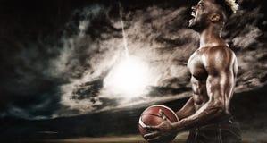 Retrato do desportista afro-americano, jogador de basquetebol com uma bola Homem novo apto no sportswear que guarda a bola fotografia de stock