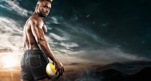 Retrato do desportista afro-americano, jogador de voleibol da praia com uma bola sobre o fundo do céu Homem novo apto dentro imagem de stock