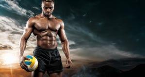 Retrato do desportista afro-americano, jogador de voleibol da praia com uma bola sobre o fundo do céu Homem novo apto dentro fotos de stock royalty free