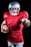 Retrato do desportista que aponta ao guardar o futebol americano Imagem de Stock