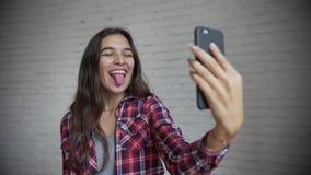 Retrato do divertimento de rir a jovem mulher atrativa com gesto do telefone à disposição que ri da câmera, no fundo cinzento vídeos de arquivo